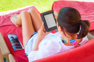 Woman reading ebook on beach chair.